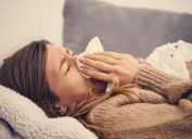 a sick woman on a couch blowing her nose with a tissue, skin cancer facts