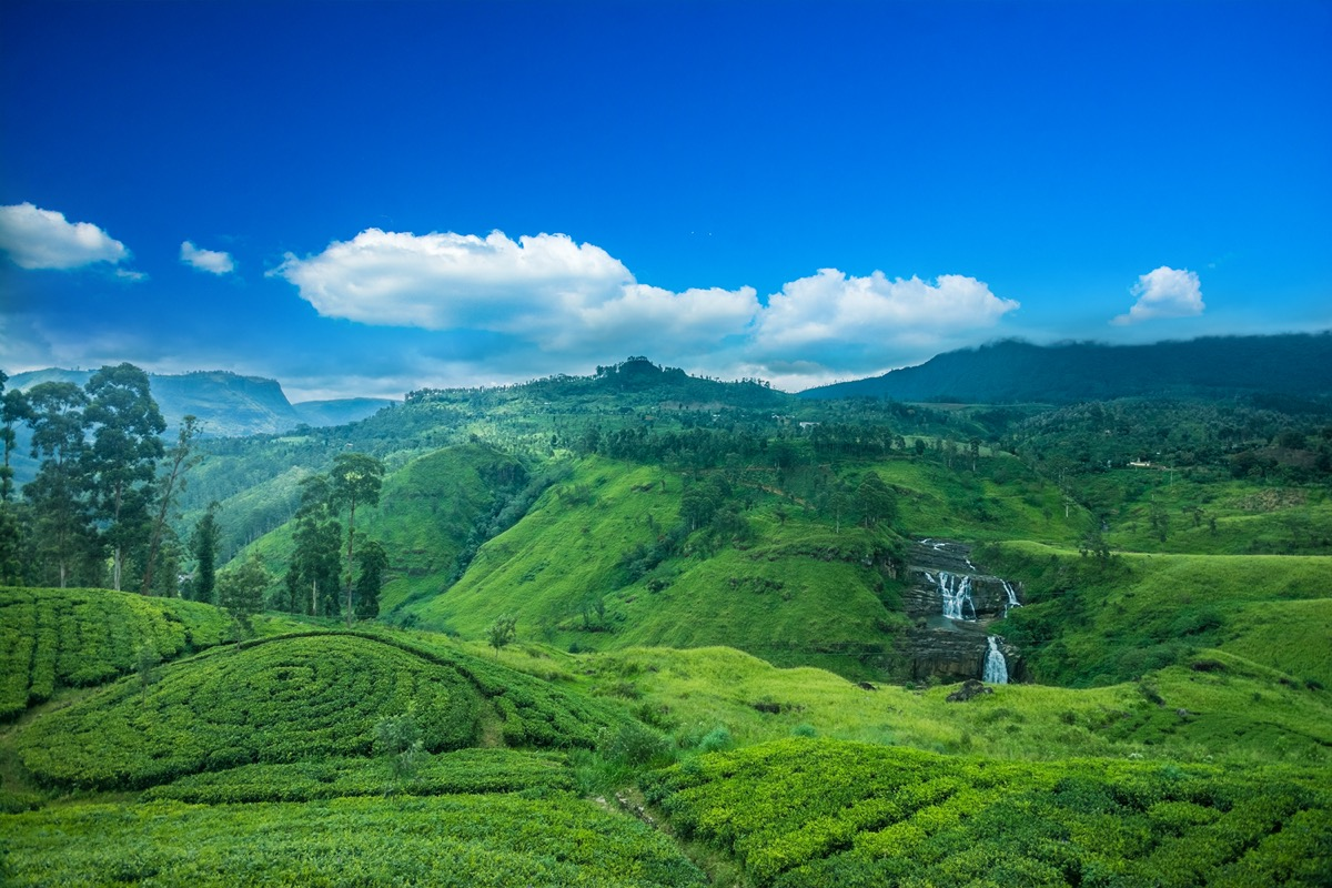 green valley, waterfalls, and blue sky in sri lanka