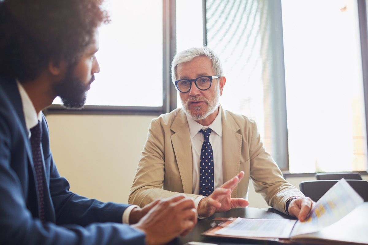 man seriously talking to his boss who appears to be upset
