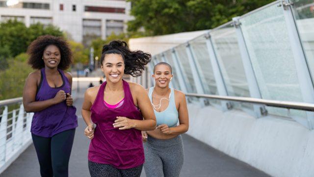 Curvy multiethnic young women jogging together on city bridge