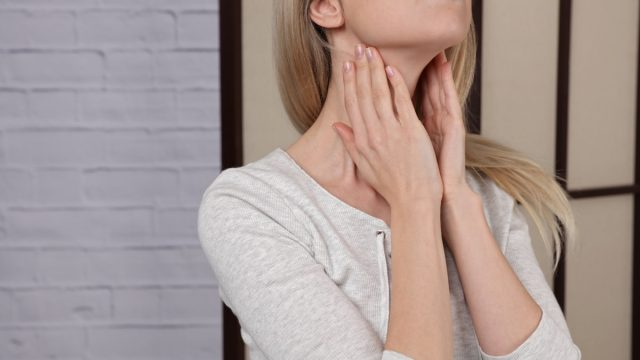 Woman Touching Her Thyroid Glands {Thyroid Problems}