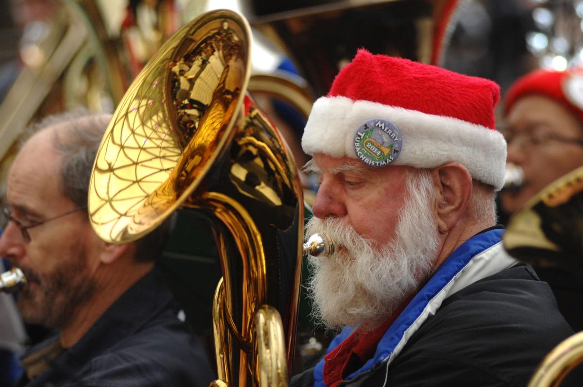 Senior man in Santa Claus hat playing tuba in a band
