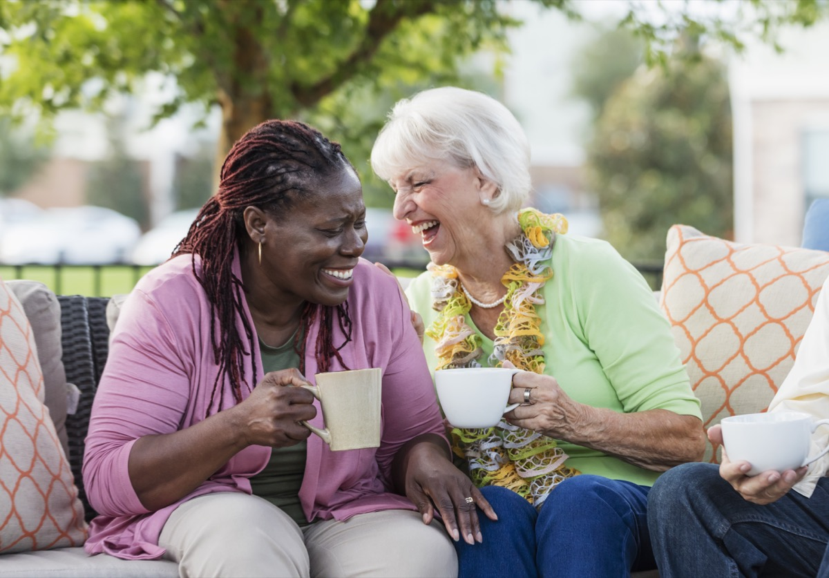 two older female friends laughing over a cup of coffee