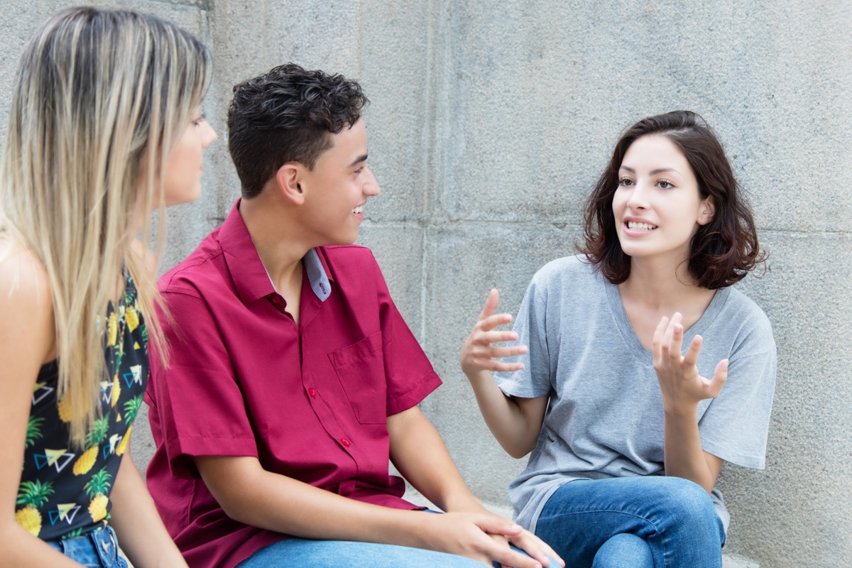Three young adults in discussion outdoors in the summer