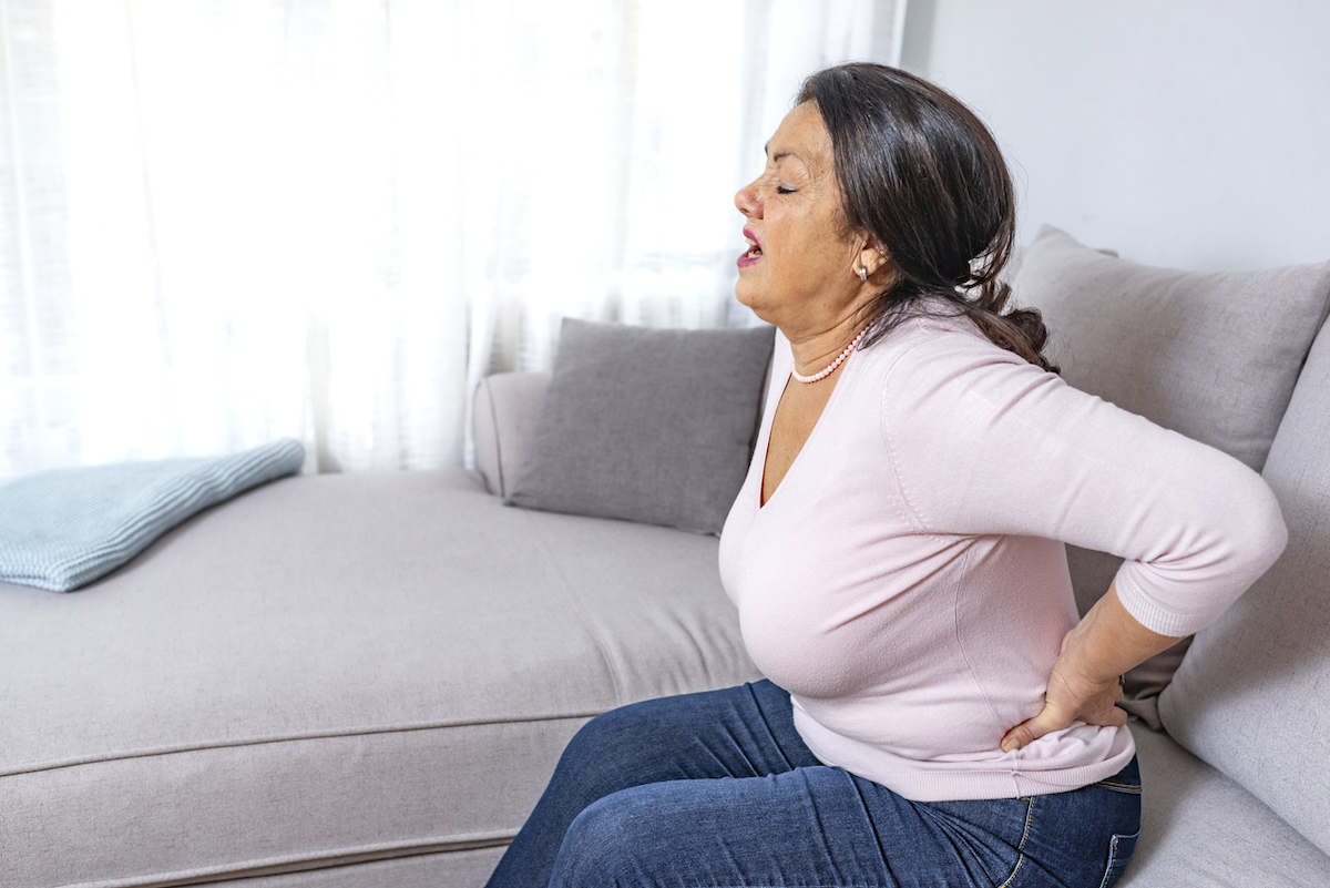 Upset mature middle aged woman feels back pain