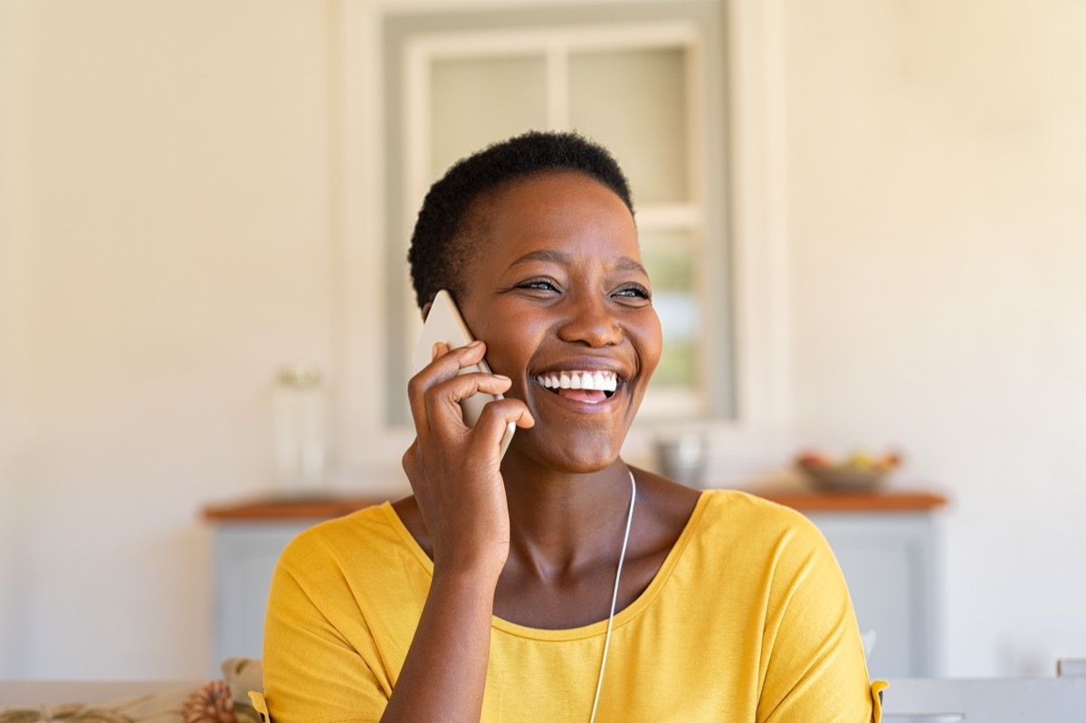 woman laughing and calling someone on the phone