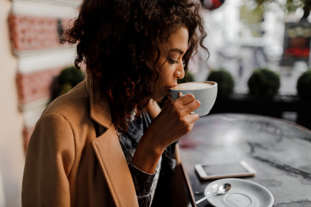 Black woman drinking a latte in a coffee shop in the winter