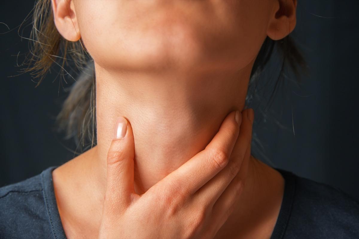 Woman Touching Her Neck in Pain {Heart Disease Symptoms}