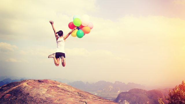 happy woman holding balloons jumping into the sky in joy