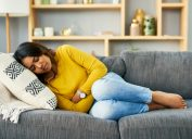 young woman suffering from stomach cramps at home on couch