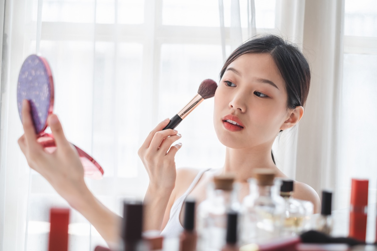 Young beautiful woman applying cosmetics make up on her face, health beauty skin care and make up concept