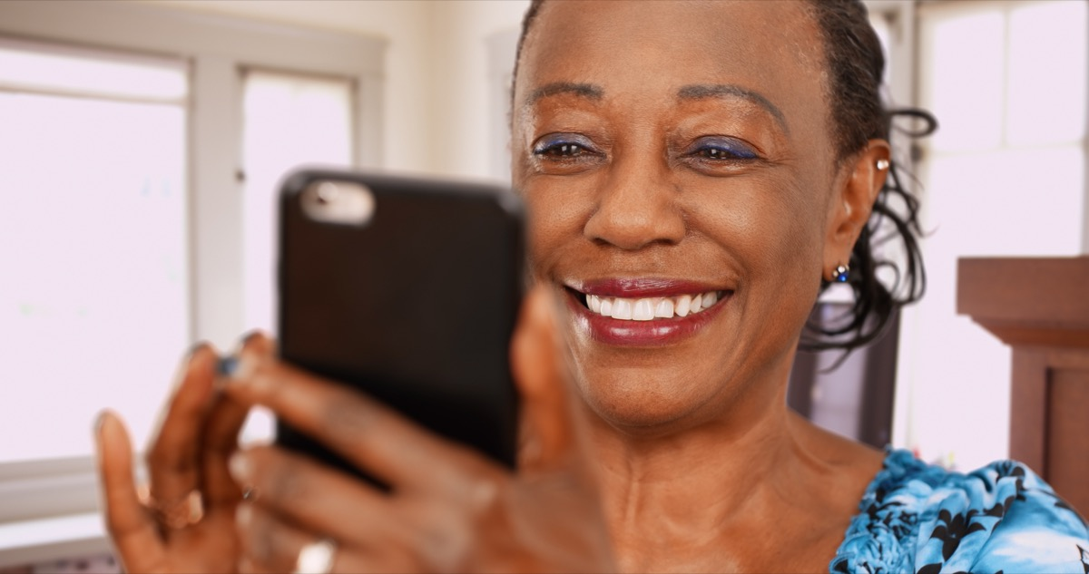 Woman smiling and looking at cell phone