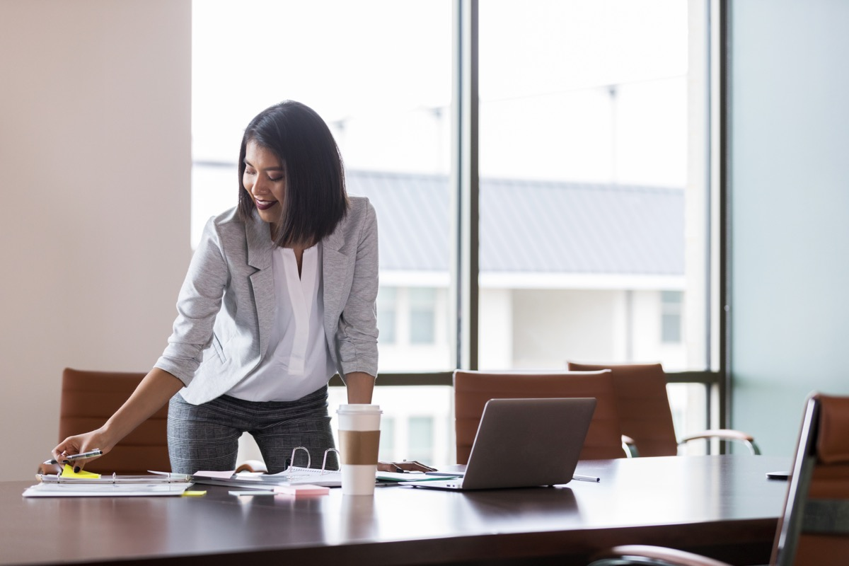 Woman smiling at work looking down at her notebook
