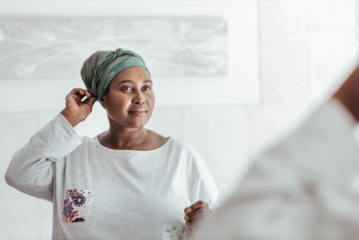 older woman over 40 smiling at herself in the mirror
