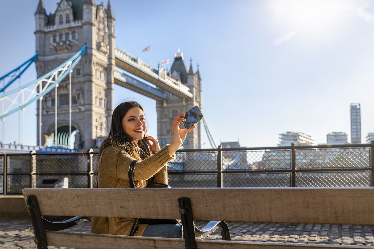 beautiful female London traveler takes a selfie picture with her phone in front of the Tower Bridge on a sunny day
