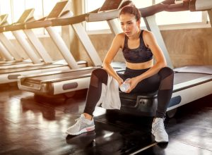 Asian young woman tired taking a break from running or exercise sitting on treadmill machine drinking water and towel sweat in fitness gym healthy .girl in sportswear workout rest in morning