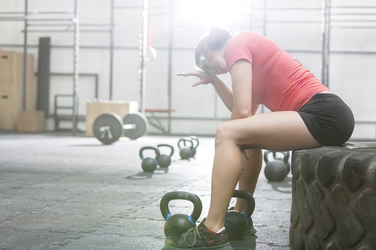 tired woman working out with kettlebells