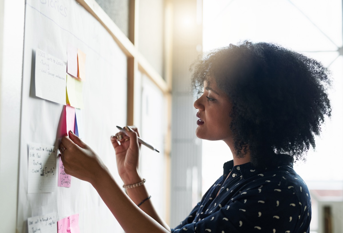 woman writing her goals on a board