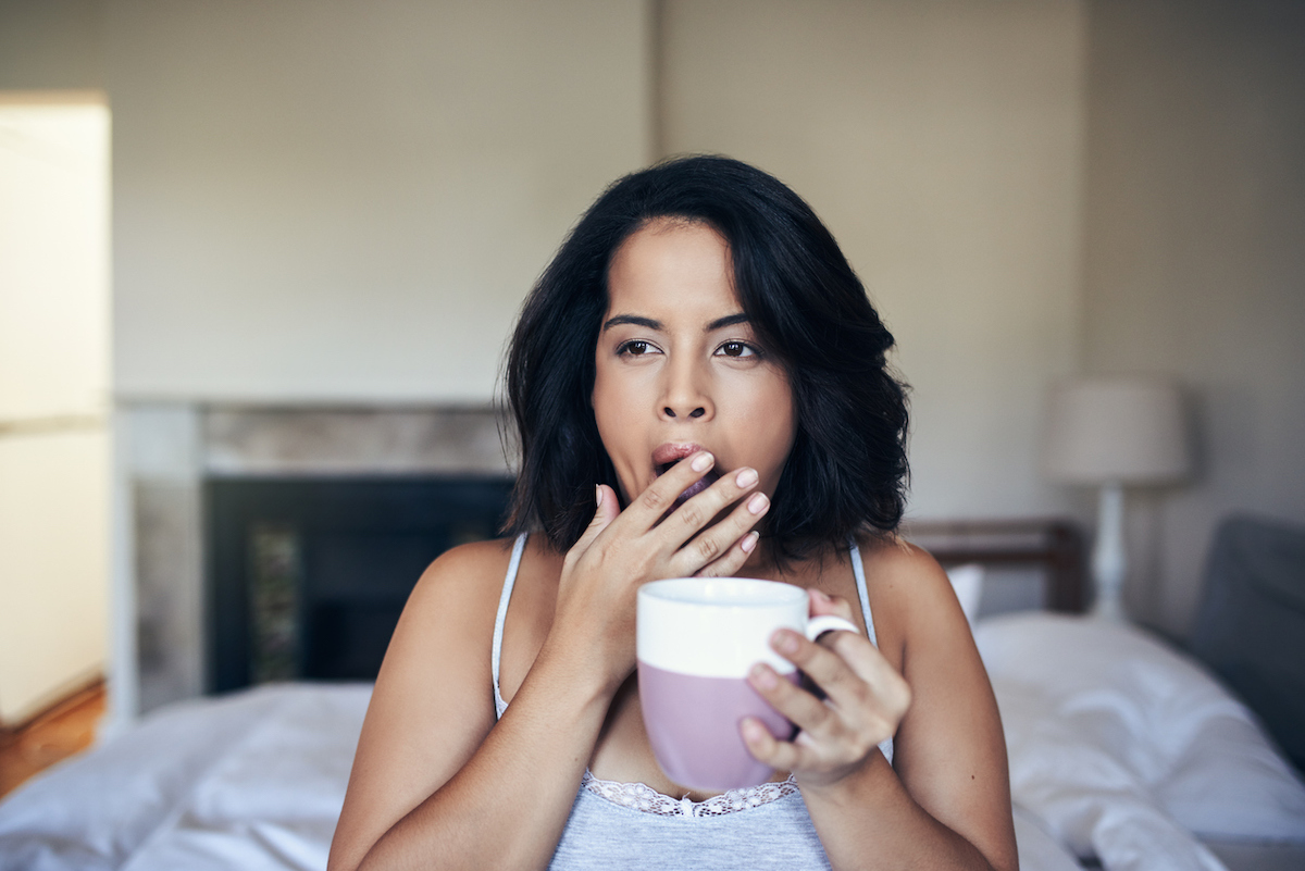 young woman yawning while having coffee in the morning at home