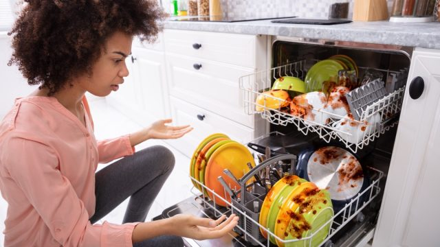 African American woman with a broken dishwasher