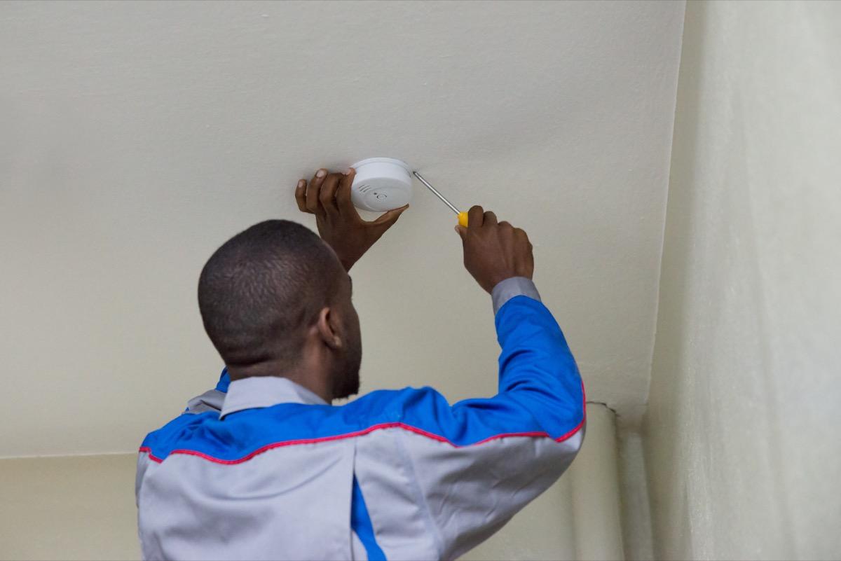 African American man installing smoke detector