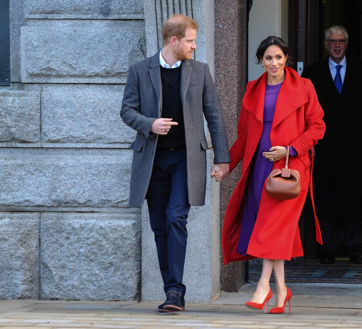 prince harry looking concerned while holding hands with meghan markle