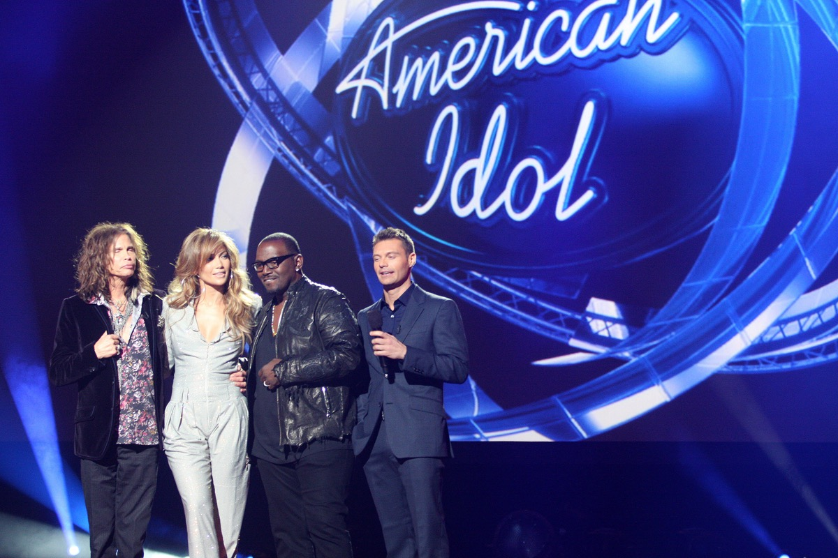 American Idol judges standing in front of the American Idol sign
