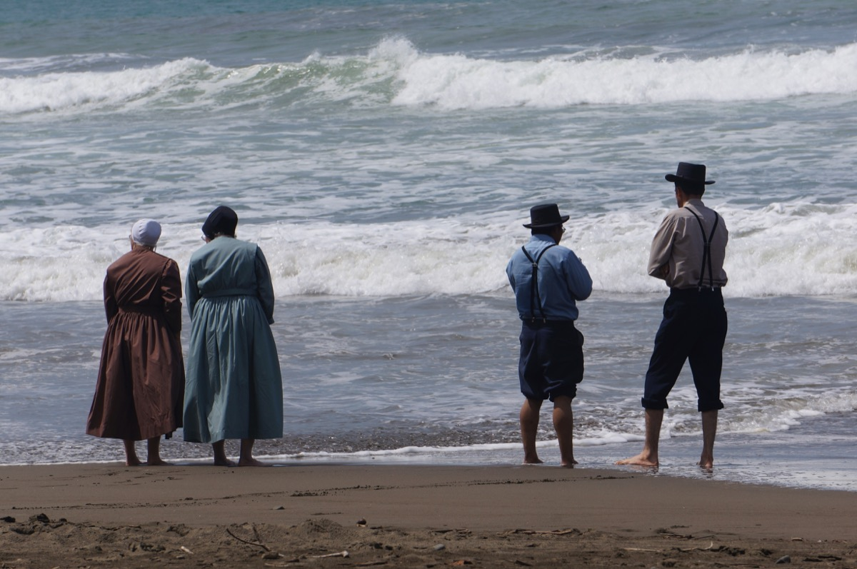 Four amish people standing on the sand in front of the beach
