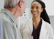 young black female doctor talking to older white male patient