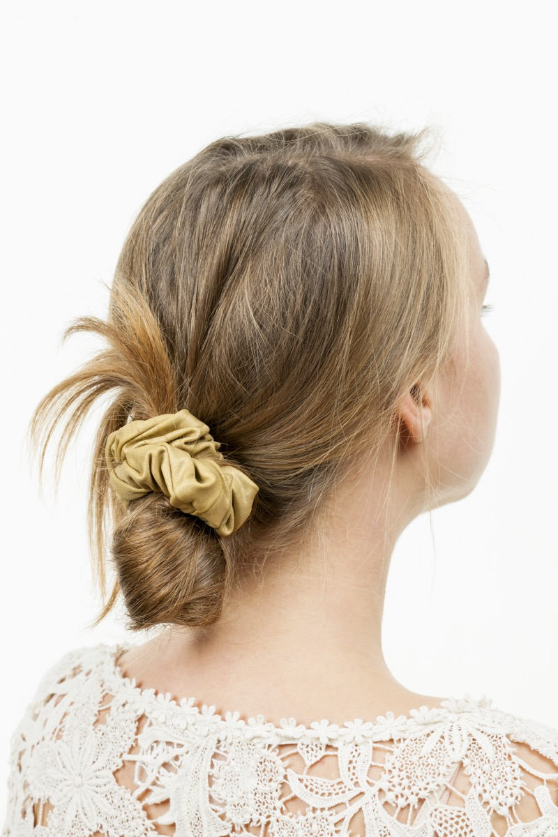 Blonde woman wearing a low messy bun with a scrunchie