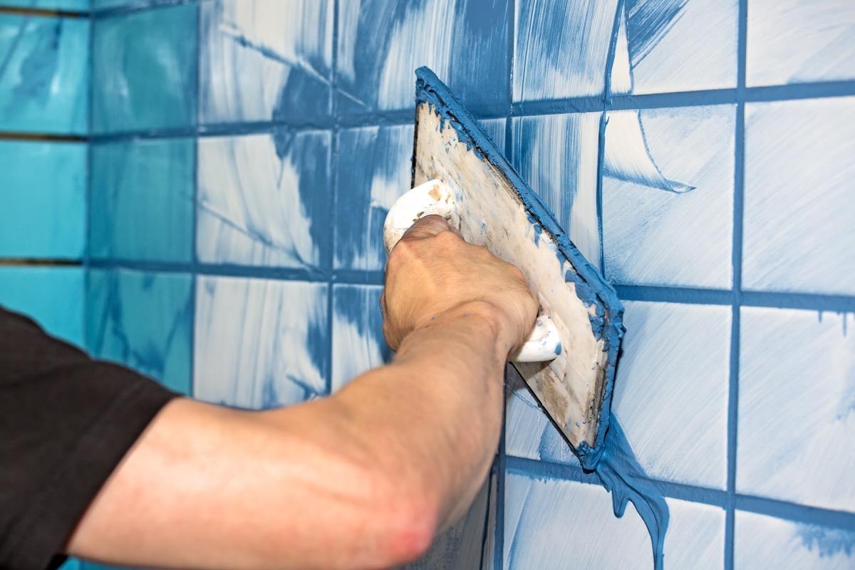Man applying blue grout tile