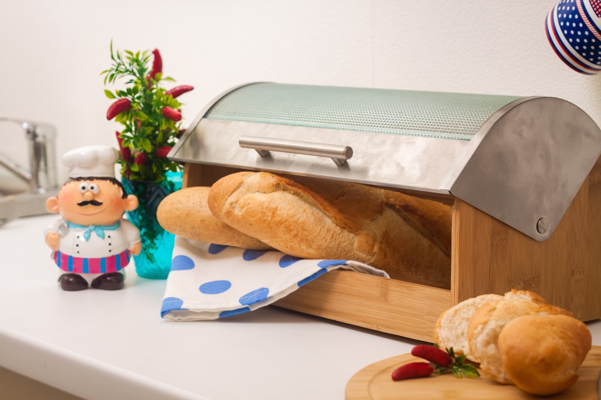 Baguette, lying in a breadbox, made of wood with metal lid