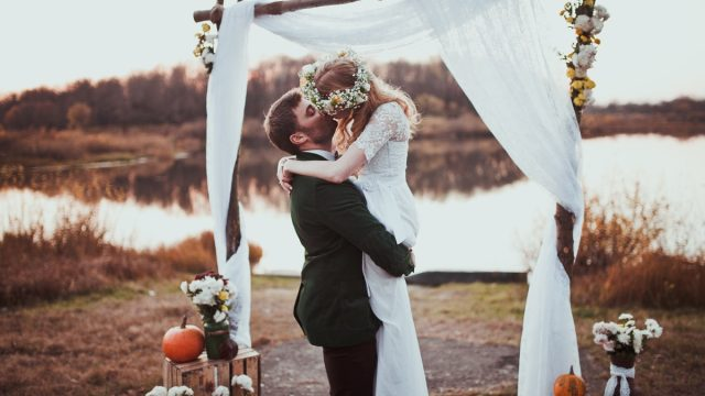 bride and groom kissing at a rustic wedding
