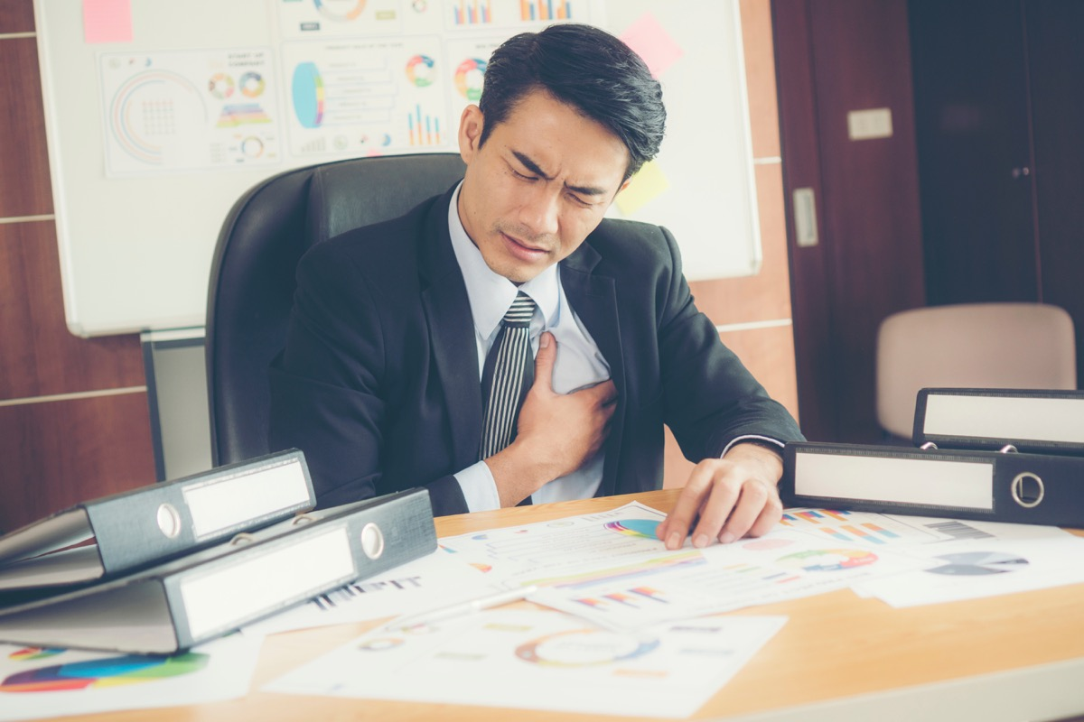 Business man experiencing heart pain at his desk