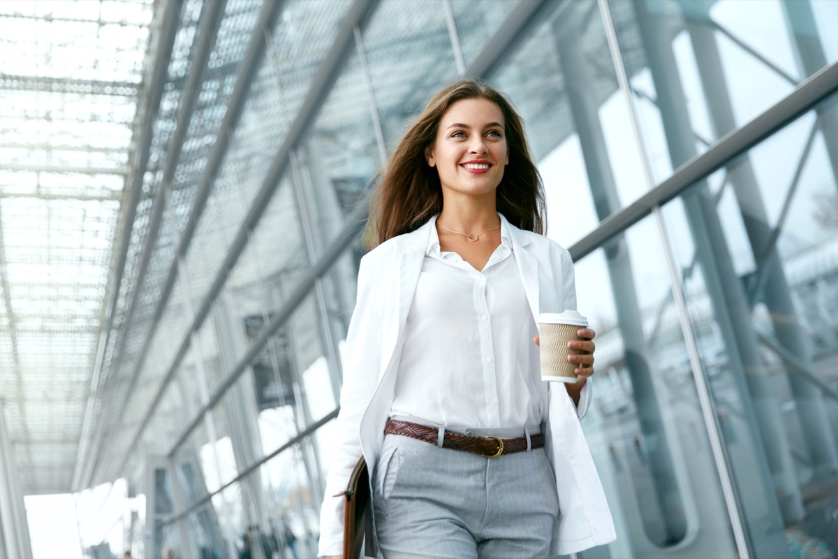 Woman Going To Work With Coffee Walking Near Office Building. Portrait Of Successful Business Woman Holding Cup Of Hot Drink In Hand On Her Way To Work On City Street health tweaks over 40
