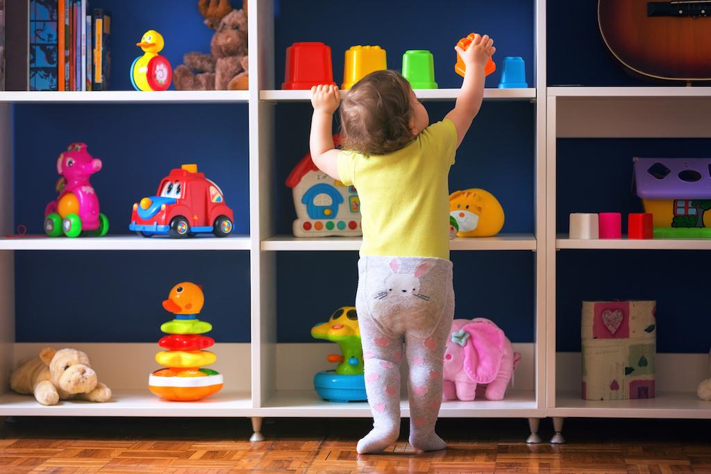 Child reaching for toy on shelf Tricks for hiding children's toys