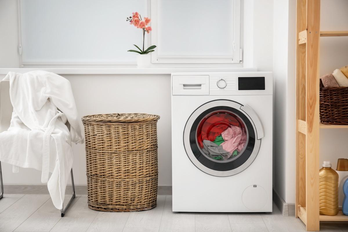 Laundry in washing machine and basket indoors - Image