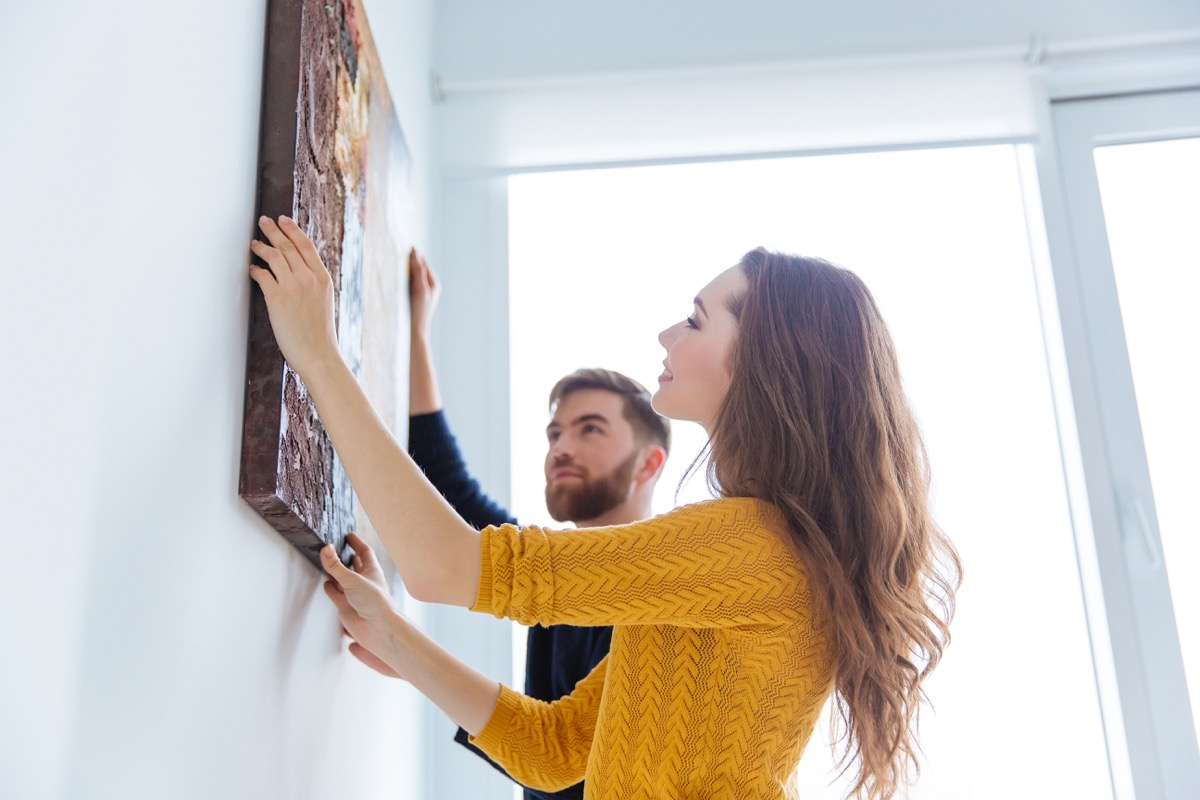 Couple hanging a piece of art in their home