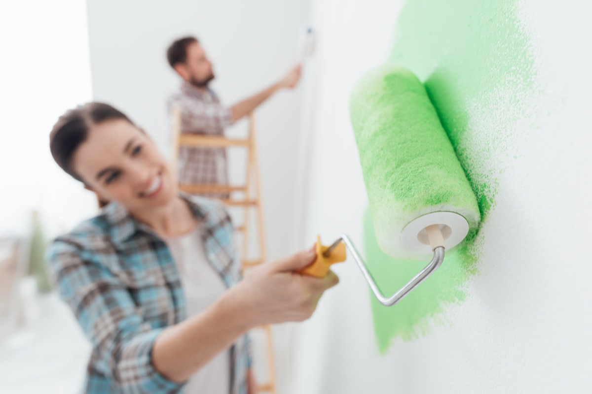 Couple roller painting a bright green wall
