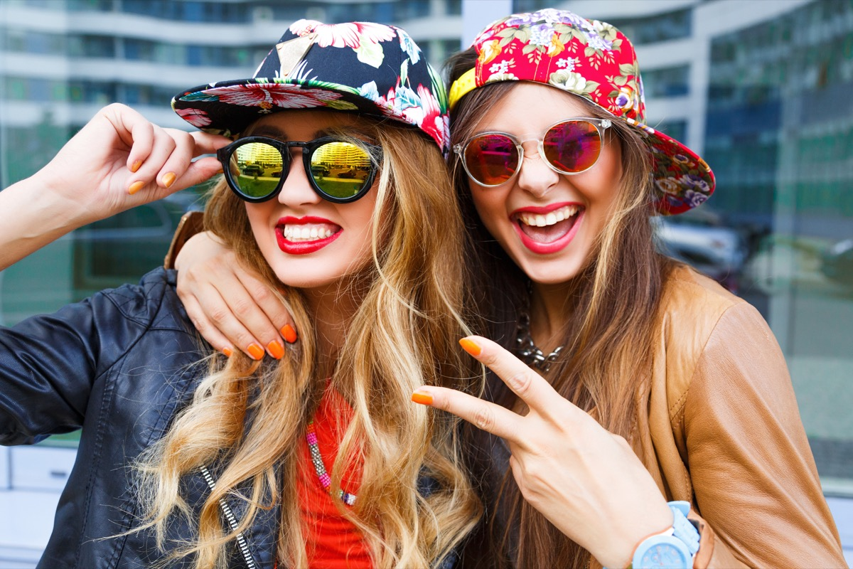 Two women wearing floral straight cap hats with sunglasses