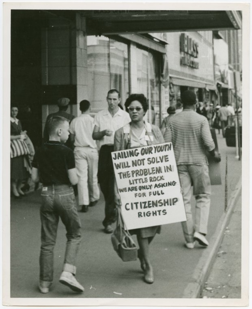 daisy bates protesting outside with sign