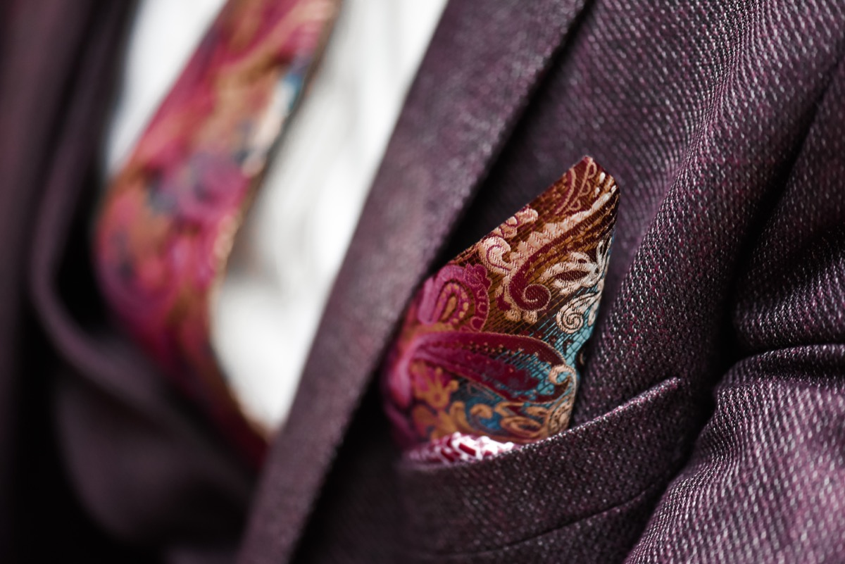 a closeup shot of a deep red jacket paired with a white shirt and a floral tie and pocket square