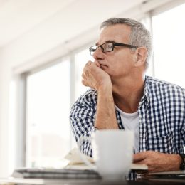 Shot of a mature man looking thoughtful while working on a laptop at home
