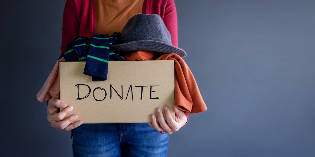 Donation Concept. Woman holding a Donate Box with full of Clothes