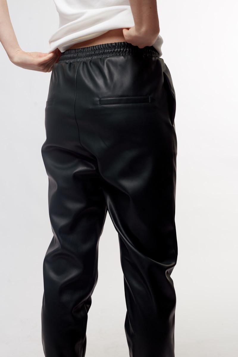 Woman wearing black leather elastic waist pants