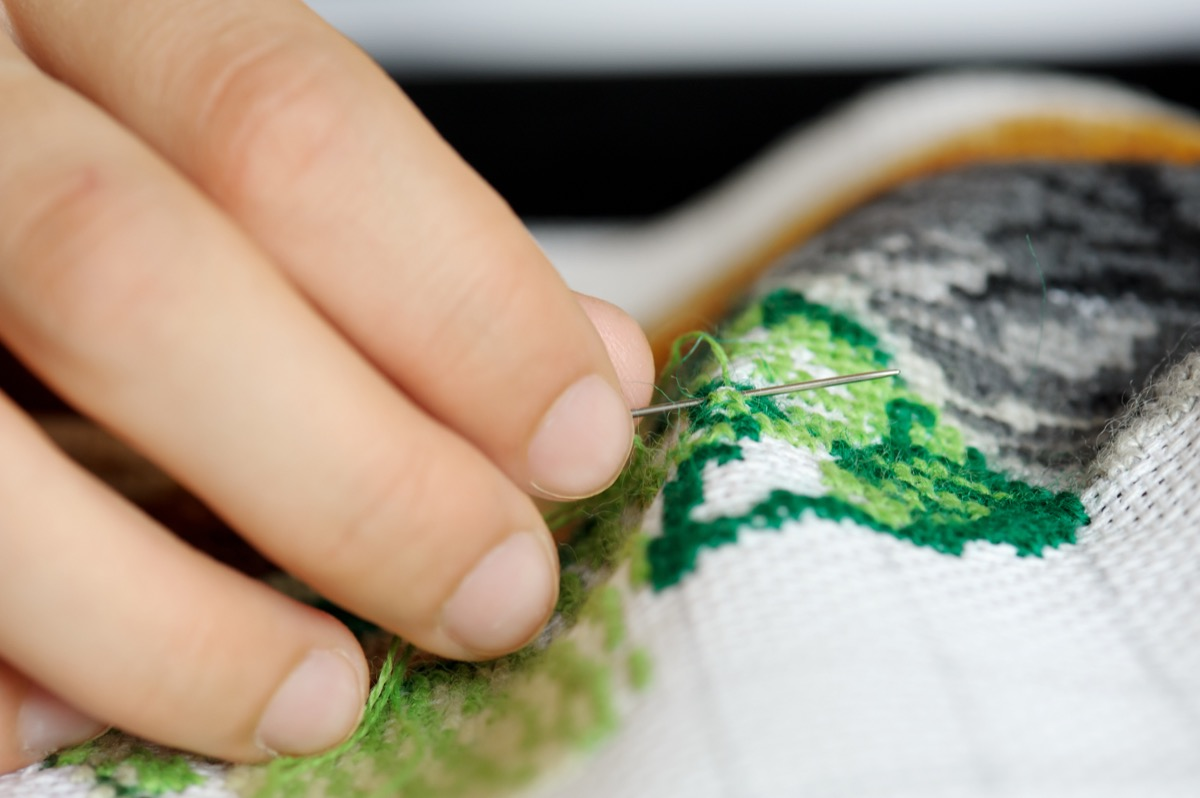 Hands of the girl working upon the embroidery, located on a black background
