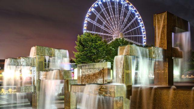 Vibrant Lights Illuminate Modern Fountain Sculpture in Night Scene with Seattle Great Wheel in Seattle, Washington