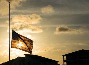 flag at half staff at sunset
