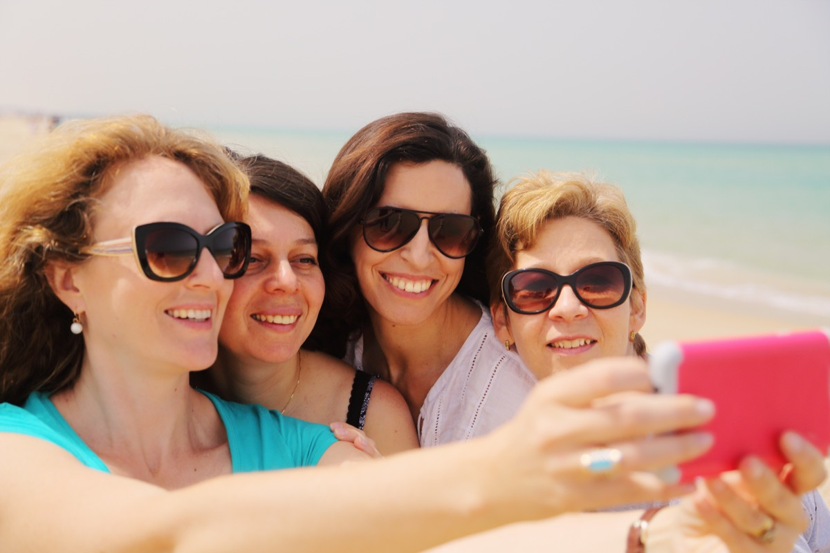 Older women smiling on the beach while taking a selfie