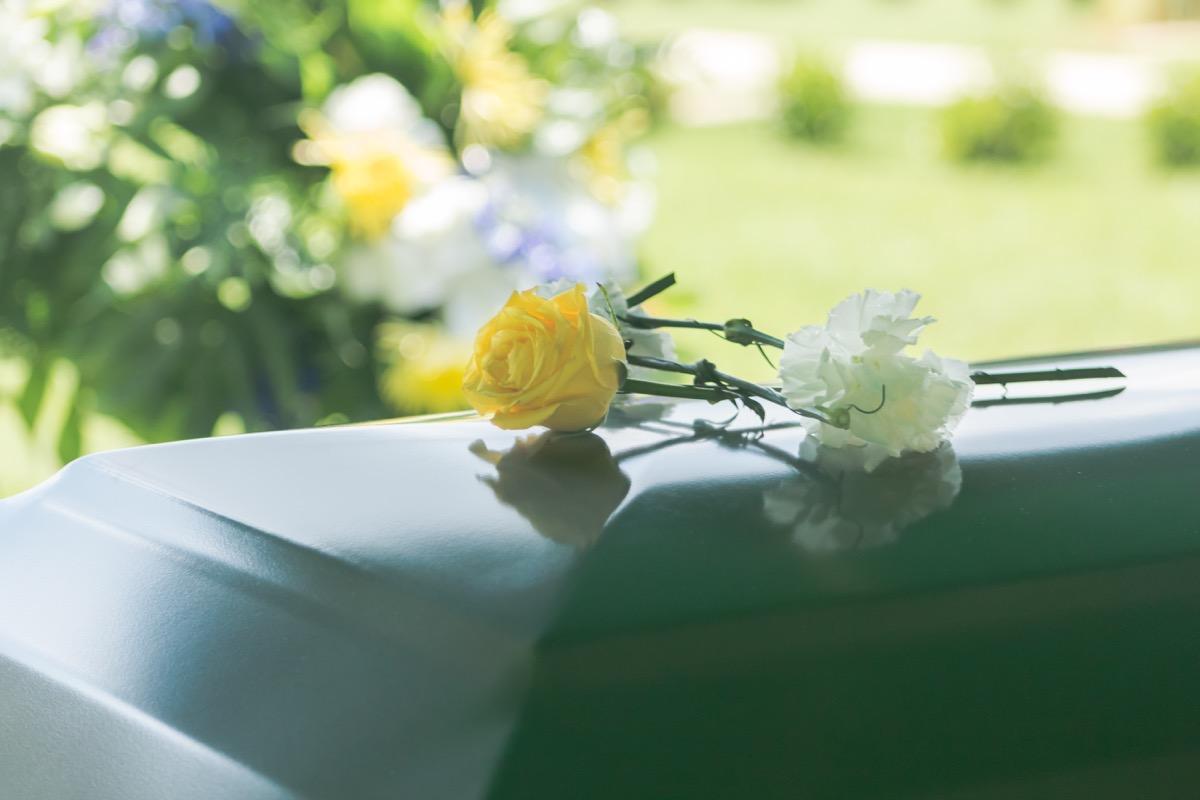 A closeup of flowers atop a funeral casket outdoors